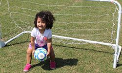 Little girl stopping a soccer ball at the net